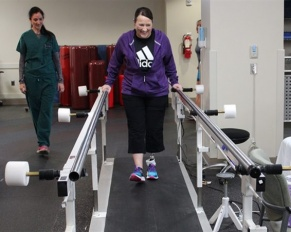 patient on treadmill working with physical therapist