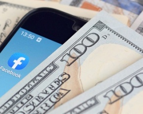smartphone with Facebook app and hundred dollar bills